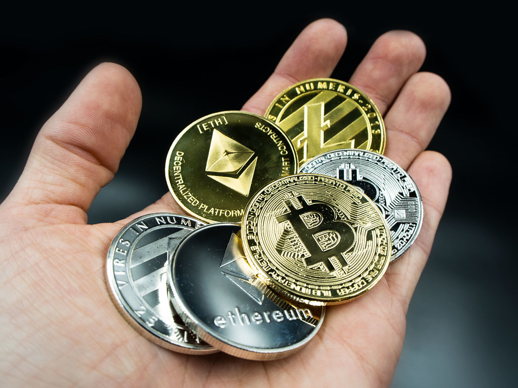 various cryptocurrency coins placed on palm of hand